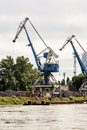 Blue cranes in cargo port translating coal, industrial scene Royalty Free Stock Photo