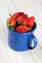 Blue cup full of fresh picked ripe strawberries a speckled on a rustic farmhouse style kitchen table filled with freshly vertical Stock Photography