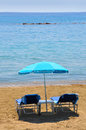Blue deckchairs under parasol on seaside Stock Photos
