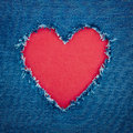 Blue denim background with red heart shape for copy space torn from jeans fabric romantic love concept Stock Photography