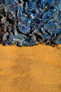 Blue desert rose piece of sahara mineral and yellow sahara sand background close up vertical orientation Stock Images