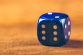 Blue dice on wooden table macro shot of with number six facing retro toned selective focus Stock Photo