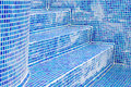 Blue dirty swimming pool tiles in bathroom with water drops Stock Photo