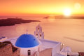 Blue dome of the church st spirou in firostefani on santorini panoramic view a island greece at sunset Stock Image