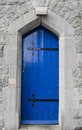 Blue door in limestone wall Royalty Free Stock Photo