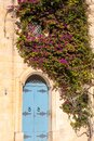 Blue door and purple flowers covering stone wall in Malta Royalty Free Stock Photo