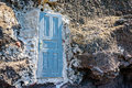 Blue door standing in the middle of the rock, leading nowhere Royalty Free Stock Photo
