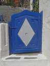 Blue door white rhombus house entrance in a mediterranean island Royalty Free Stock Image