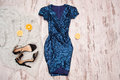 Blue dress in sequins, black shoes and halves of orange. Wooden background, fashionable concept Royalty Free Stock Photo