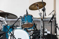 Blue drum set and plates standing on outdoor stage against wall