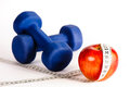 Blue dumbbells and red apple with measure tape Royalty Free Stock Photo