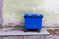 Blue dumpster against a bright green wall cleaning and recycling in city Royalty Free Stock Images