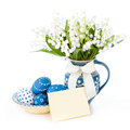 Blue easter decorations on white background eggs painted and spring flowers in matching vase Royalty Free Stock Photo