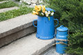 Blue enamel jugs on stone steps retro metal old in back yard house garden Royalty Free Stock Photography