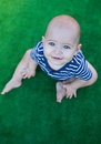 Blue-eyed baby sitting on green fundal. Royalty Free Stock Photo