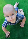 Blue-eyed baby walking crawl, green fundal. Royalty Free Stock Photo