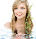 Blue-eyed blonde with bamboo in water Royalty Free Stock Image