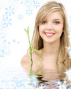 Blue-eyed blonde with bamboo in water Stock Images