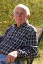 Blue eyed elderly man sits outside Royalty Free Stock Photo