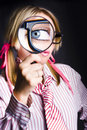 Blue eyed nerd enlarged pupil looking magnifying glass spying unsolved business clues Royalty Free Stock Image
