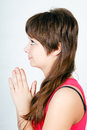 Blue-eyed teen girl praying. profile Stock Photo