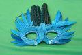 Blue feather mask on green background Royalty Free Stock Photo