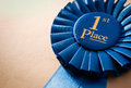 Blue first place winner rosette or badge from pleated ribbon with central text to be awarded to the of a competition on a Royalty Free Stock Photography
