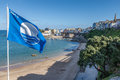 Blue flag beach at tenby pembrokeshire showing the clue waving in the wind and the town behind Stock Photo