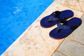 Blue flip flops at the edge of a swimming pool pair Stock Image