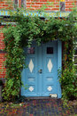 Blue  front door in a historic house with climbing plants at the Royalty Free Stock Photo