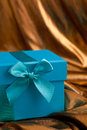 Blue gift box with a bow on gold fabric close up of decorative matching ribbon and draped Stock Photos