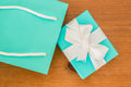 Blue gift box and ribbon a white boy with a bag on a wooden table Stock Photo