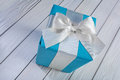 Blue gift box with white bow on white wooden table Royalty Free Stock Photo