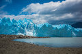 The blue glacier is illuminated by the rays of the sun. Shevelev. Royalty Free Stock Photo