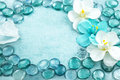 Blue glass drops aqua with white flowers orchid and bar of sea s Royalty Free Stock Photo