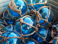 Blue glass fishing floats with rope knot netting piled in a bucket Stock Images