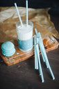 Blue glass of milk with french macaroon on wood board Royalty Free Stock Photo