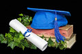 Blue graduation cap on old books with ivy and white diploma tied with ribbon Royalty Free Stock Photos