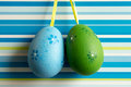 Blue and green hanged Easter eggs on striped background Royalty Free Stock Photo
