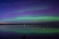 Blue green and purple aurora borealis reflected over a lake