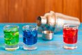 Blue green red alcohol or alcohol free cocktail with ice cubes and shaker on a bar counter wooden background Stock Photos