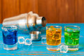 Blue green red alcohol or alcohol free cocktail with ice cubes and shaker on a bar counter wooden background Royalty Free Stock Photo