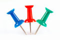 Blue, green and red pushpins stuck in the white paper Royalty Free Stock Photo
