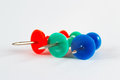 Blue, green and red  pushpins on the white paper closeup Royalty Free Stock Photo