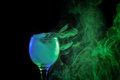 Blue and green smoke in a glass. Halloween.