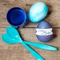 Blue greeting card with easter eggs, egg spoons and egg dyes, te Royalty Free Stock Photo