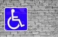 Blue handicap parking or wheelchair on wall brick .