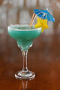 Blue hawaiian cocktail served on a busy bar top garnished with a carambola slice and an umbrella Stock Photography