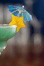 Blue hawaiian cocktail served on a busy bar top garnished with a carambola slice and an umbrella Stock Images