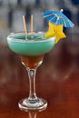 Blue hawaiian cocktail served on a busy bar top garnished with a carambola slice and an umbrella Royalty Free Stock Photography
